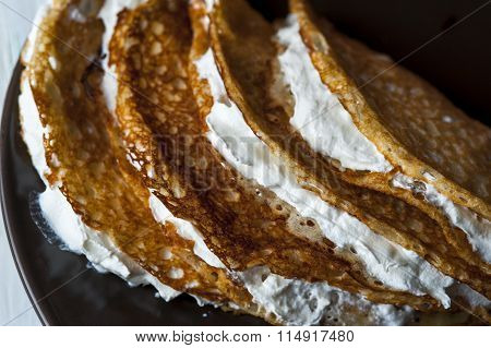Pancakes with whipped cream on brown plate