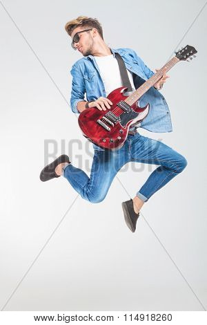 guitar player jumping and looking back in studio while playing rock and roll