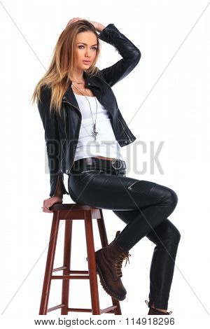 attractive woman in leather jacket posing seated in studio background while arranging her hair and looking away