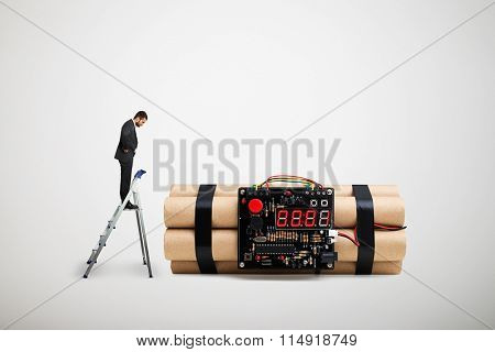 small businessman standing on the stepladder and looking at big bomb over light grey background