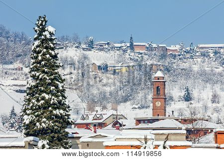 Big tall tree and small italian town covered with snow on background in Piedmont, Northern Italy.