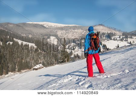 Hiker Man Resting In Winter Mountains,standing On A Snow-covered Slope, Looking Into The Distance.