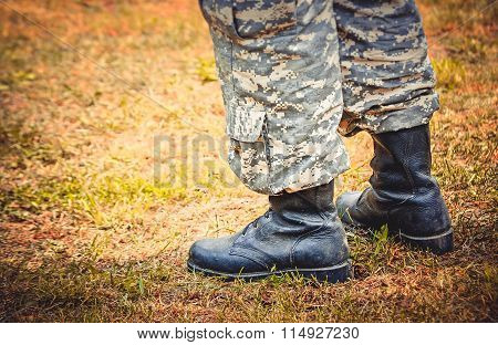 man stands in military boots and trousers