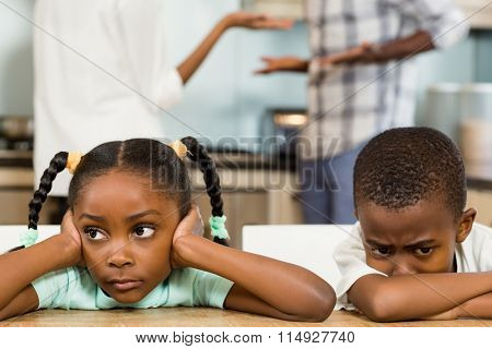 Sad siblings against parents arguing in kitchen
