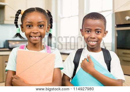 Cute siblings ready for school looking at the camera in the kitchen