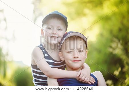 Two Adorable Little Brothers Laughing And Hugging On Warm And Sunny Summer Day