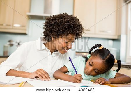 Mother checking her daughter's homework in the kitchen