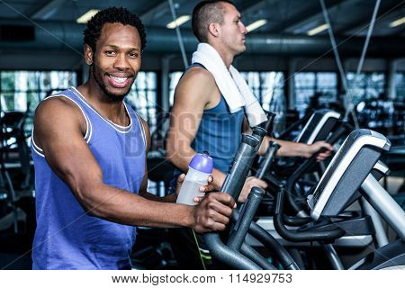 Smiling man using elliptical machine at gym