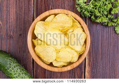 Chips in a wooden bowl, greens, and cucumbers on an