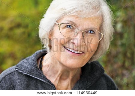 Senior lady looking relaxed and happy in font of nature background