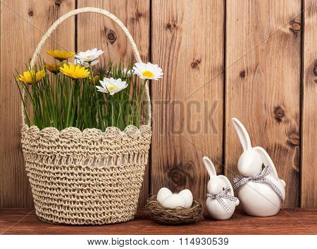 Easter decoration - basket with flowers, bunnies with easter eggs in the nest.