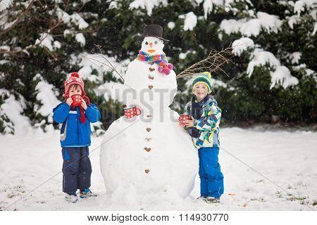 Happy Beautiful Children, Brothers, Building Snowman In Garden