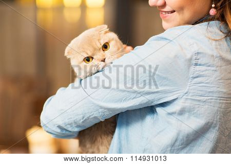 happy woman holding scottish fold cat at home