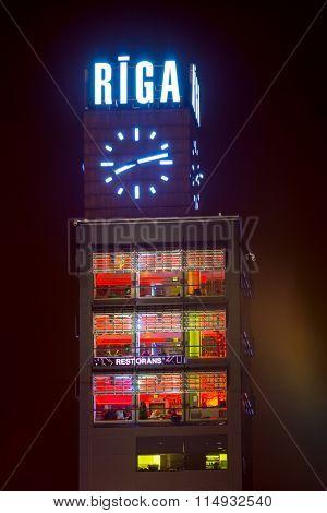 RIGA, LATVIA - DECEMBER 20, 2015: Tower clock and restaurant at evening on December 20, 2015 in Riga, Latvia