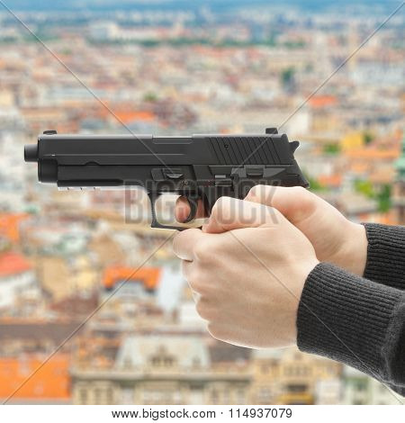 Man With A Handgun Ready To Shoot - Focus On Handgun And Blurred Scenery Of City On Background