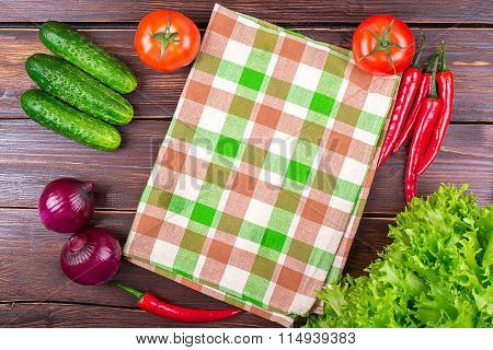 Towel, cucumbers, hot pepper, lettuce leaves, onion, and fresh tomatoes on an