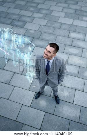 businessman with world map hologram outdoors