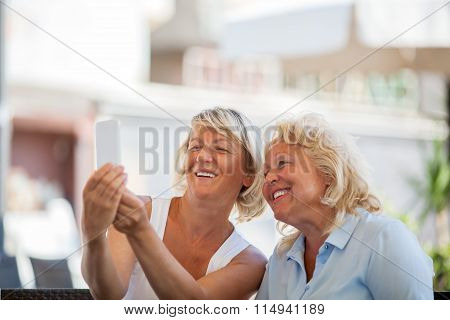 Happy senior women making mobile selfie