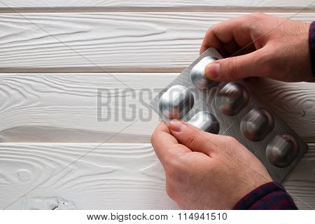 Man Opens A Package Of Antibiotics Tablets On A White Background
