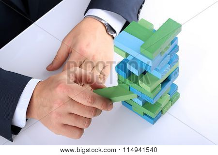 Planning, Risk And Strategy In Business, Businessman  Getting   Out A  Wooden Block From A Tower