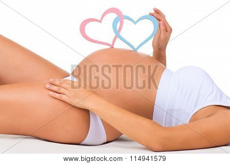 Close-up Belly Of Pregnant Woman. Gender: Boy, Girl Or Twins? Two Hearts