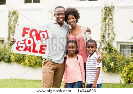 Happy family standing together while holding a sold sign