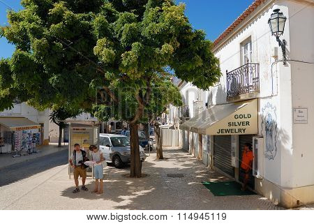 Tourists check map in the shadow on a hot day at the street in Lagos, Portugal.
