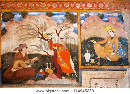 Men And Woman Relaxing Outdoor And Drinking Tea On The Colorful Mural Of Palace Chehel Sotoun In Ira