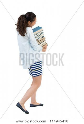 A girl carries a heavy pile of books. back view. Rear view people collection.  backside view of person.  Isolated over white background.  Swarthy girl in summer clothes carries textbooks