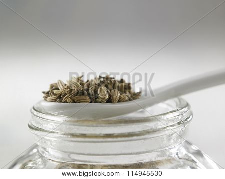 spoon of cumin on top of glass container