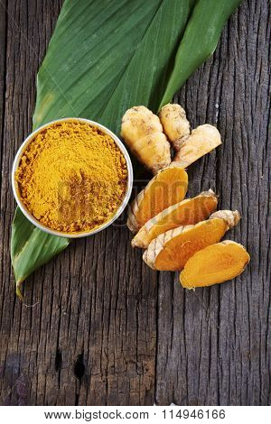 top view of turmeric powder and leaf on the wooden background