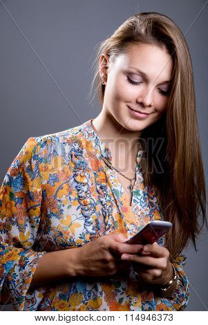 Portrait Of A Young Beautiful Girl In A Bright Colored Blouse Looking At Mobile Phone