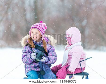 little girl and her sister sitting on a sled in the winter park