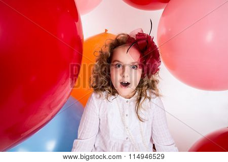 Surprised Girl In A Hat Of The Bow Against The Backdrop Of A Large Bright Airy Rubber Balls