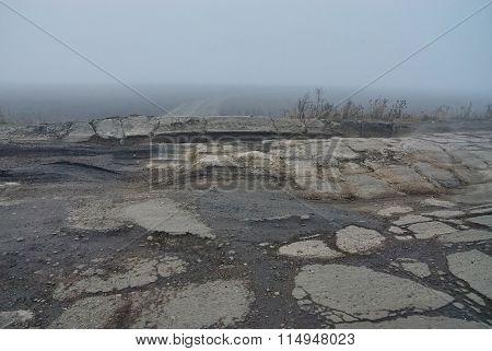 Damaged Asphalt Road With Potholes In Fog