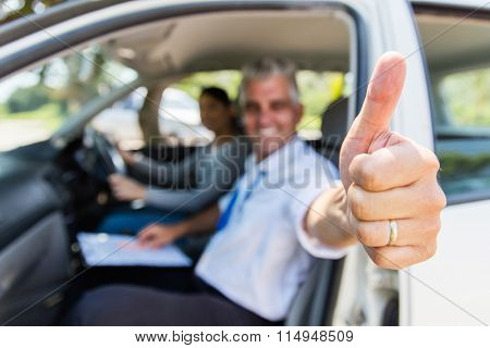 driving school instructor with learner driver giving thumb up