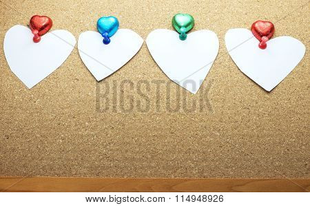 White papers in heart shape with colorful push pins and heart chocolates on bulletin /cork board