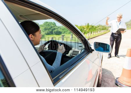 happy young student driver with driving instructor learning to park a car