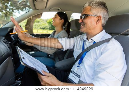 smiling young girl with driving instructor taking lessons