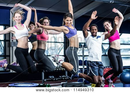 Fit group smiling and jumping in gym