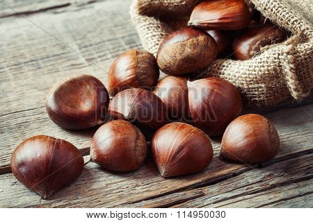 Edible Chestnuts In Bag On Rustic Kitchen Table.