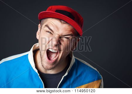 Portrait Of Screaming Young Guy In Studio.