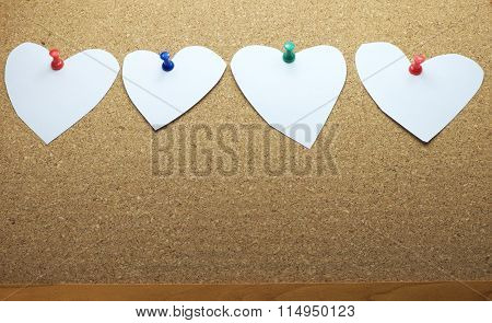 White papers in heart shape with colorful push pins on bulletin board, cork board