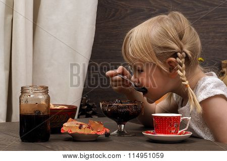Little girl eating jam. On the table, a cup, jam, sweets