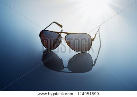 Sunglasses on blue reflective background.
