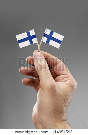 Man holding two small flags of Finland in his hand.
