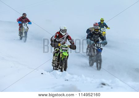 group young racers drive on snowy motocross track