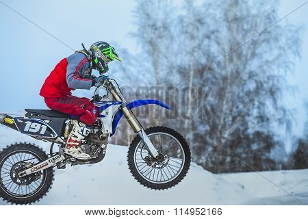closeup of motorcycle racer in background of snowy motocross track