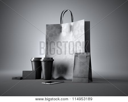Set of black shopping bag, two coffee cups, blank business cards and generic design smartphone. Dark