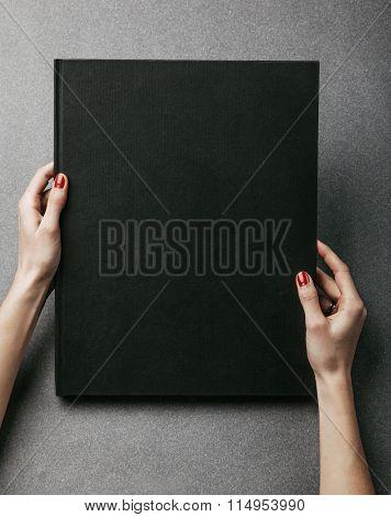 Female hands holding big black book. Vertical